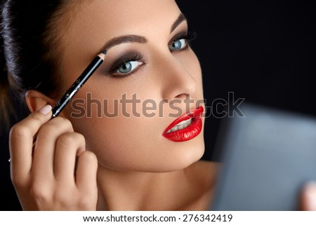 Make-up. Beautiful Woman Doing Makeup Eyebrow Pencil. Red Lips  - stock photo