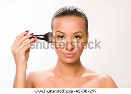 Make up. Brown sleek hair beautiful woman with fan brush close to face.