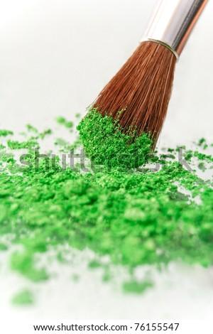 make-up brush and crushed green cosmetic powder isolated white background - stock photo