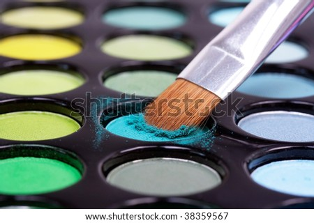 Make-up brush in blue eyeshadows - stock photo