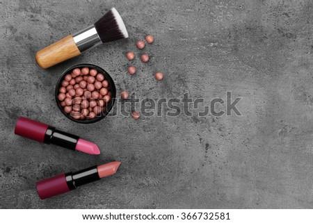 Make-up brush, lipsticks, eye-shadow and blusher, on grey background - stock photo
