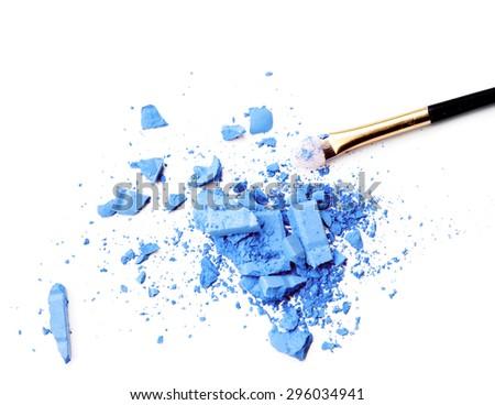 make-up brush on blue crushed eyeshadow - stock photo