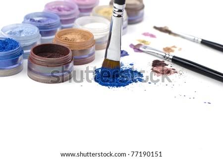 make-up brush on colorful crushed eyeshadow - stock photo