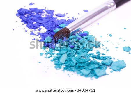 Make-up brush on crumbled blue eye shadows - stock photo