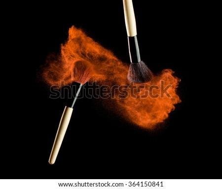 Make-up brush with powder explosion on black background - stock photo