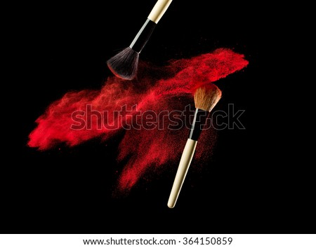 Make-up brush with powder explosion on black background - stock photo