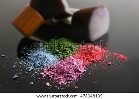 Make up brushes and colourful eye shadows on black background