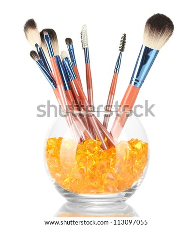 Make-up brushes in a bowl with stones isolated on white - stock photo