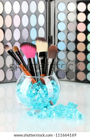 Make-up brushes in a bowl with stones on palette of shadows background