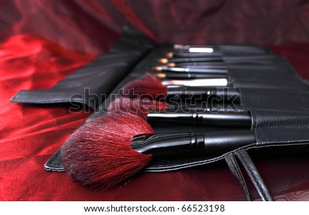 make-up brushes in a handbag - stock photo