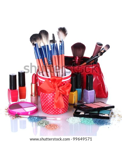 make-up brushes in cup and cosmetics isolated on white - stock photo