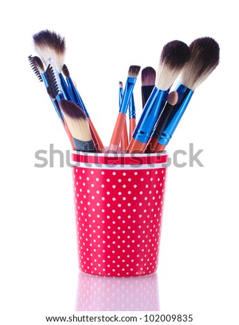 make-up brushes in red cup isolated on white