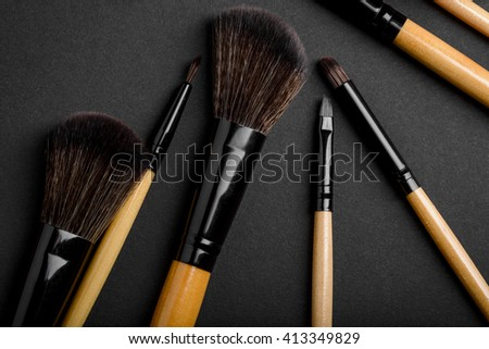 Make-up brushes of different types in foreground. Professional instruments for putting make-up on the grey table. Chinese, lip, eyeliner and eyeshadow brushes for flawless visage. - stock photo