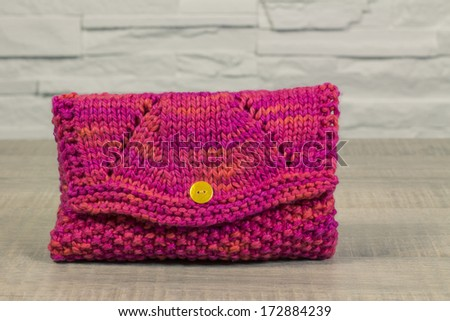 Make up case, small pink handbag knitted on a vintage table - stock photo