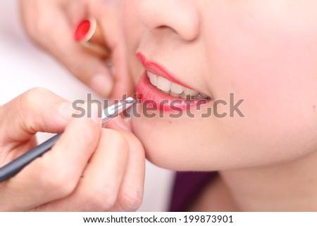 Make-up closeup apply red lipstick. - stock photo