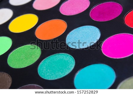 Make-up colorful eyeshadow palette over black closeup - stock photo
