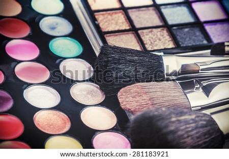 Make-up colorful eyeshadow palettes with makeup brushes. Focus in the middle of the frame on the orange brush. Shallow depth of field. Toned image - stock photo