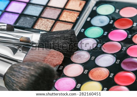 Make-up colorful eyeshadow palettes with makeup brushes. Focus in the middle of the frame on the black brush. Shallow depth of field - stock photo