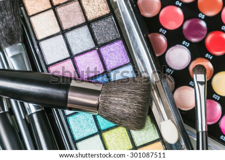 Make-up colorful eyeshadow palettes with makeup brushes. Focus on the brush. Shallow depth of field - stock photo