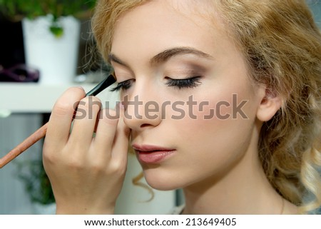 Make up. Cosmetic. Make-up artist applying color eyeshadows on model's eye, close up. Applying Make-up.  - stock photo