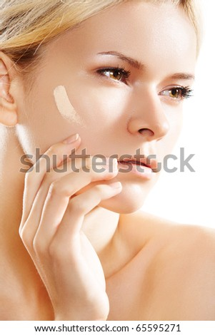 Make-up & cosmetic. Woman applying skin foundation on white backgroun. - stock photo