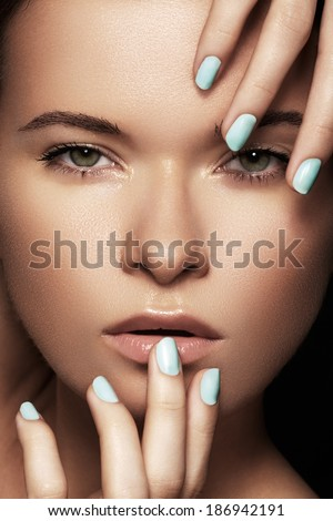Make-up & cosmetics, manicure. Close-up portrait of beautiful woman model face with clean skin on white background. Natural skincare beauty, clean soft skin, manicure. Suntan girl with sky blue nails