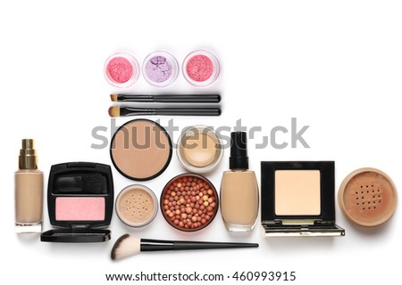 Make-up cosmetics set of liquid and cream foundations, compact and loose powder in various tones, bronzing pearls, blush, eye shadows and brushes isolated on white background. Top view point.