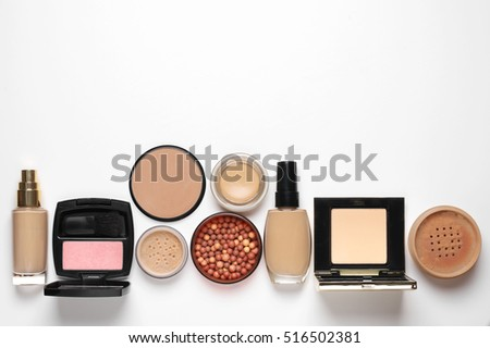 Make-up cosmetics set of liquid and cream foundations, compact and loose powder in various tones, bronzing pearls and blush on white background. Top view point.