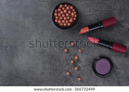 Make-up lipsticks, eye-shadow and blusher, on grey background - stock photo
