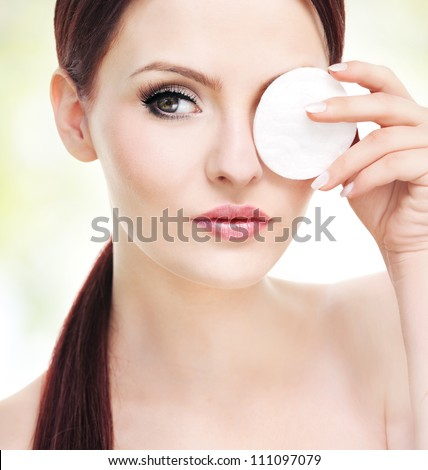 Make up removal concept, beautiful young adult woman with cotton pad - stock photo