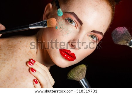 make up woman with makeup brushes.  Beautiful Face. Makeover. Perfect Skin. Applying Makeup. Make-up girl, woman teenager face with make up brushes and a blusher. Woman posing on black background - stock photo