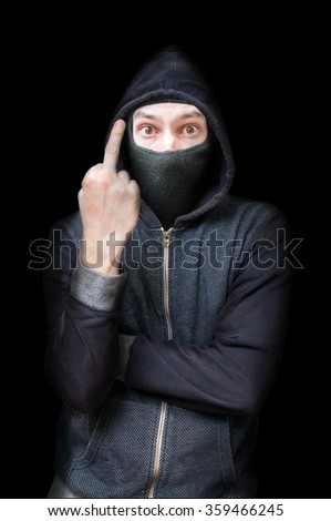 Maked rude criminal or bandit showing middle finger. Low key isolated on black. - stock photo