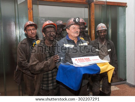 Makeevka, Ukraine - November 26, 2013: Miners with coal symbolic ingot at the ceremony in honor of 2000000 tons of coal mined in Makeevka in the current year - stock photo
