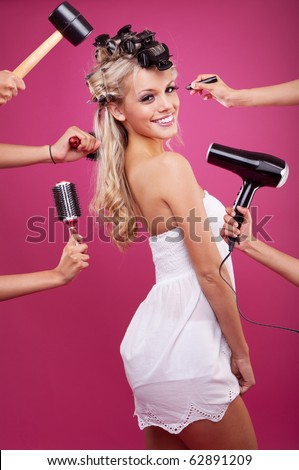 makeover studio process of a young pretty girl on pink background. many hands. - stock photo