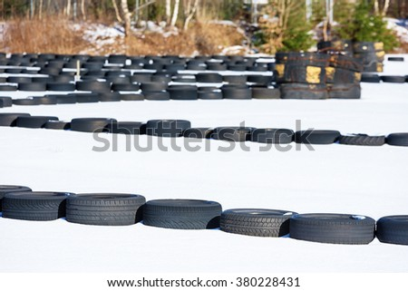 Makeshift outdoor kart circuit or racetrack in an old abandoned industrial area in winter. A thin layer of snow cover the racetrack and lots of black old tires are spread out to form the track itself.