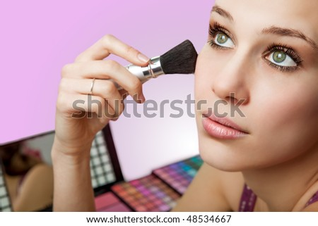 Makeup and cosmetics - beautiful woman using blush brush - stock photo