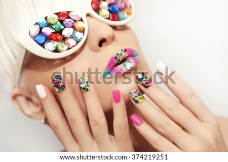 Makeup and manicure with multicolored crystals and glasses on the blonde girl. - stock photo