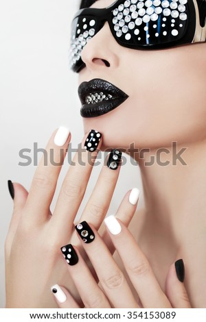 Makeup and manicure with rhinestones and white with black nail Polish.