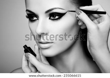 Makeup artist applies eye shadow. Beautiful woman face. - stock photo