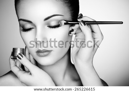 Makeup artist applies eye shadow. Beautiful woman face. Perfect makeup. Black and white - stock photo