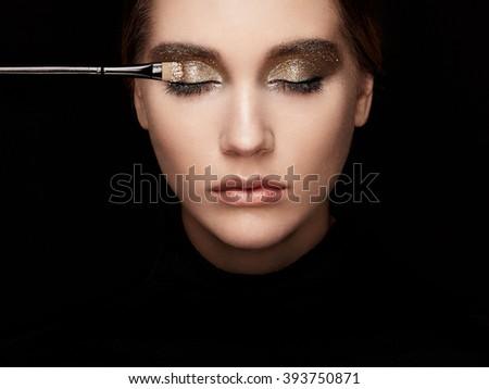 Makeup artist applies eye shadow. Beautiful woman face. Perfect makeup. Lips. Cosmetic Eyeshadow. Make-up detail. Eyeliner - stock photo