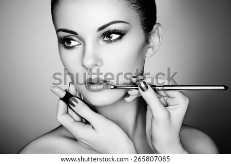 Makeup artist applies lipstick. Beautiful woman face. Perfect makeup. Black and white - stock photo
