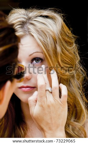 Makeup artist applies makeup to photoshoot model - stock photo