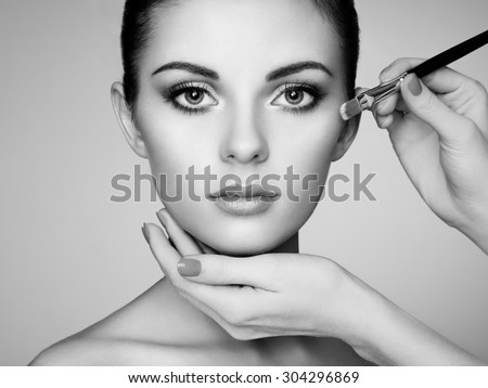 Makeup artist applies skintone. Beautiful woman face. Perfect makeup. Skincare foundation. Black and white