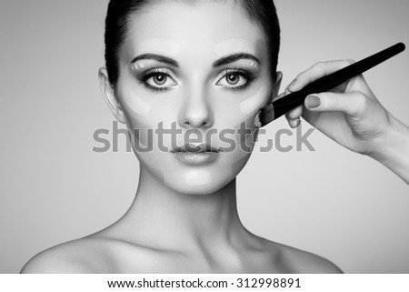 Makeup artist applies skintone. Beautiful woman face. Perfect makeup. Skincare foundation. Black and white - stock photo