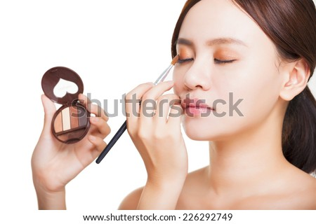 Makeup artist applying colorful eyeshadow on model's eye with a eyeshadow palettes - stock photo