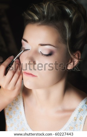 Makeup artist applying eye shadow on beautiful young woman with selective focus