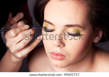 Makeup artist applying eye shadow to a young female model.