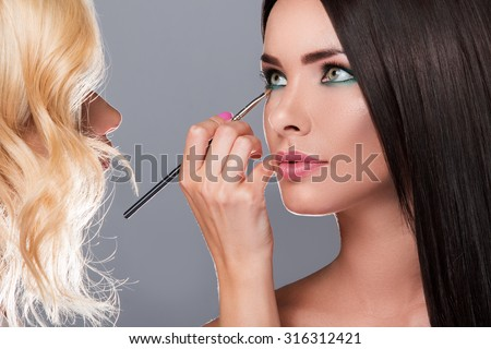 Makeup artist applying eyeshadow on model eyes in studio