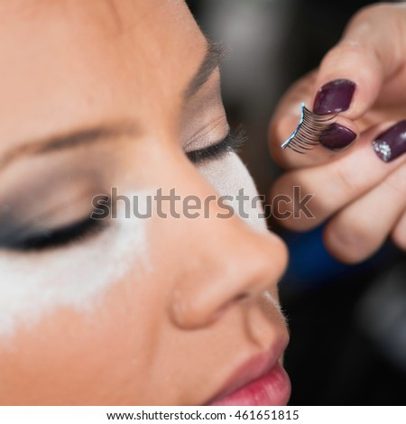 Makeup artist applying false eyelashes